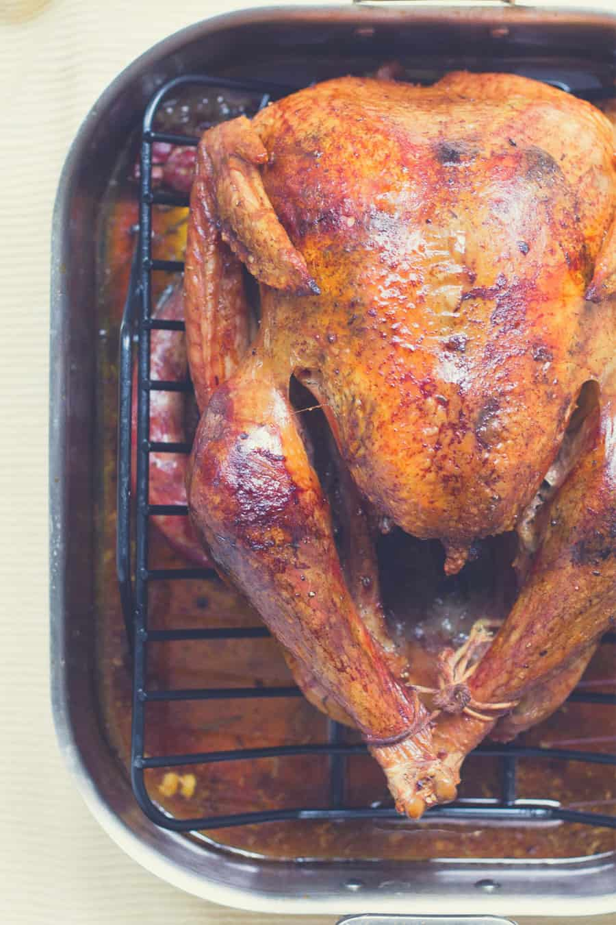A freshly smoked whole chicken is placed on a roaster - poultry smoking times