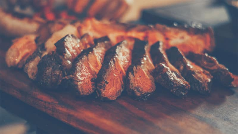 Cut brisket on a wooden board - what is a brisket - beef smoking times