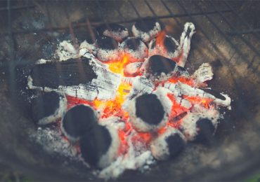 Lit charcoal chunks in a grill - the best charcoal grills under $500