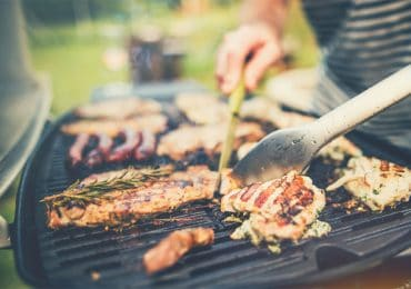 Meat is turned on electric grill with tongs - best portable electric grills