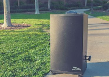 Electric smoker placed next to grass - best propane smoker - best electric smoker