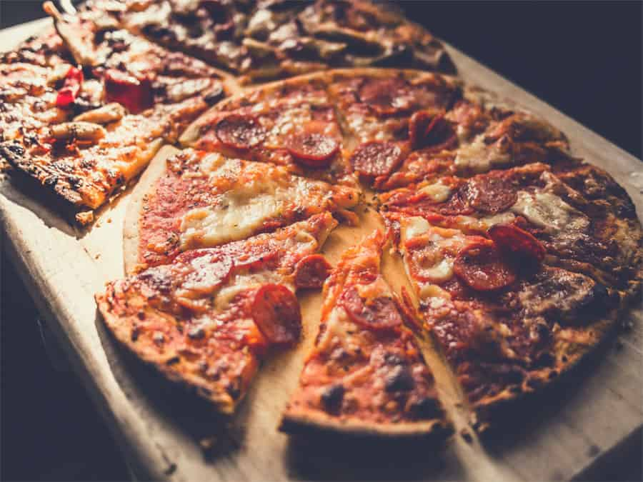 Pizza on a wooden board - best pizza stones for grills