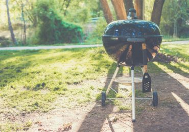 A portable charcoal stands on grass in a park - best portable charcoal grills